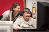 Caregiver And Mentally Disabled Woman Learning At The Computer poster