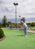 picture of miniature golf  - Lady putting on the dogleg of a miniature golf course - JPG