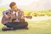 Постер, плакат: Handsome Man Playing Guitar On Green Grass