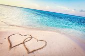 Two hearts drawn on sand of a tropical beach at sunset. Clear turquoise ocean. Maldives islands. poster