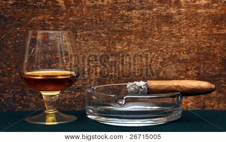 smoking cigar in an ashtray and glass cognac on dark background