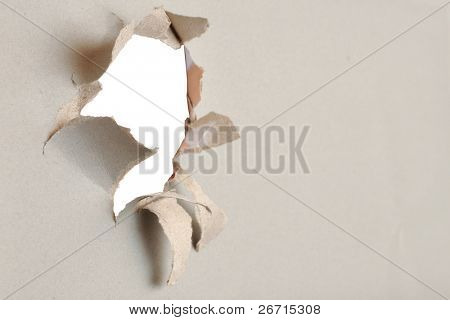 Torn paper - gray cardboard ripped apart showing underlying layer