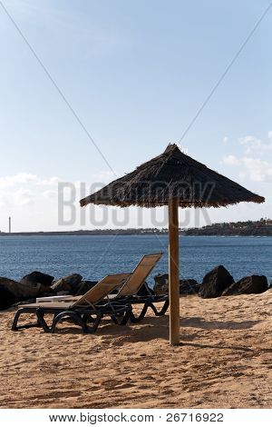 A picturesque dark brown beach umbrella and striped chaise lounges on yellow beach sand