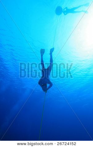 Freediver descends into blue water while safety diver floats at the surface