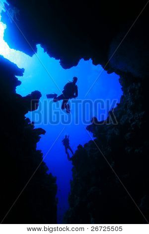 Scuba Diver descends into underwater canyon