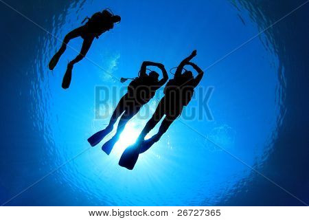 Underwater Image of Scuba Divers silhouetted against sun. Two Students practice skills under the supervision of Diving Instructor