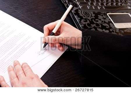 close-up of a woman's hand holding pen and signing papers