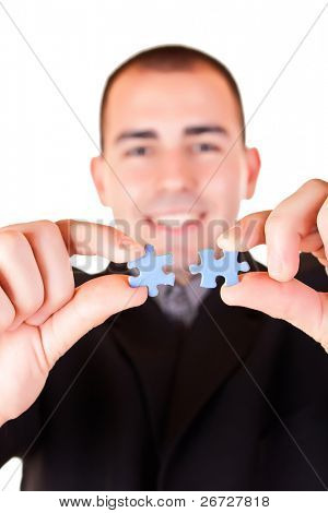 smiling businessman holding puzzle - metaphor for solution