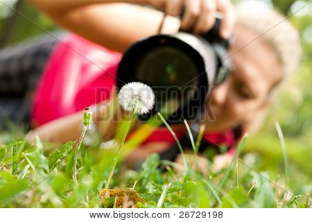 photographer, female  photograph with camera taking a macro  picture of flower