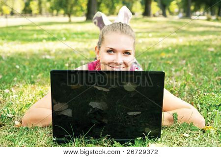 cute woman lying on grass and peeking behind laptop in park