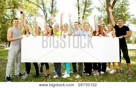 large group of people holding big white paper for advertisements, they are standing in the nature with their arms up and looking at the camera