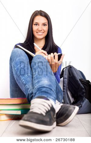 beautiful student doing homework in school hallway for time break