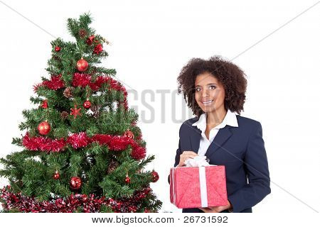 smiling afro woman holding gift box and standing next Christmas tree, isolated on white background