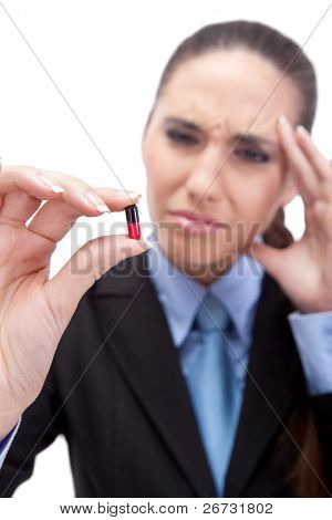 businesswoman have headache and looking in pill, pill in focus, isolated on white background