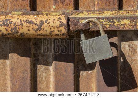 Padlock Closing Rusty Metal Door