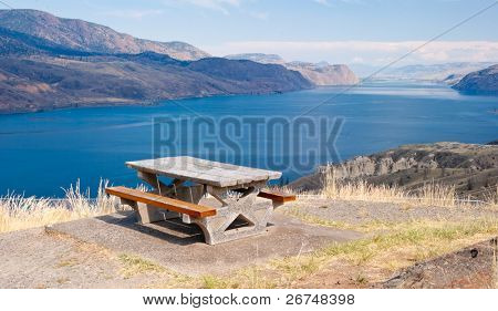 Picnic table over fantastic view at mountain lake.