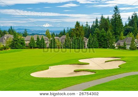 Beautiful golf place with gorgeous green and fantastic snow mountain view over blue sky with white clouds.