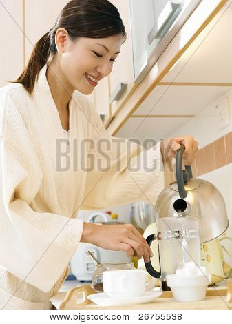 A lady pouring hot water into the tea pot