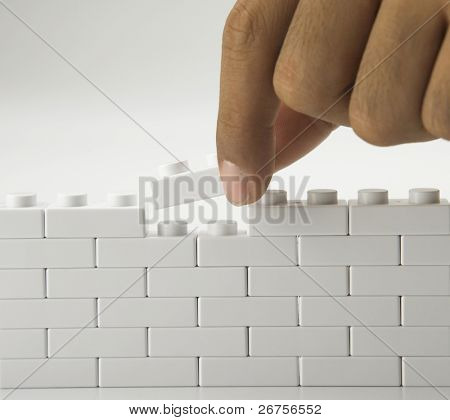 man building up a wall by stacking up
