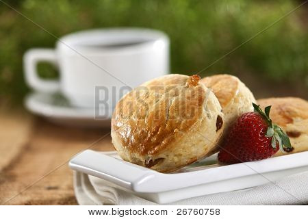 Scones decorated with strawberry and a cup of coffee.