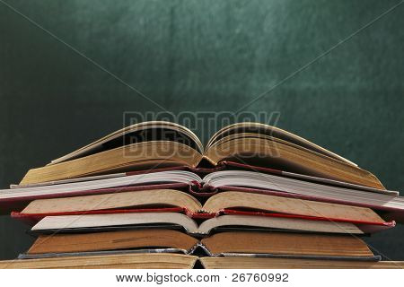 stack of books in front of the blackboard