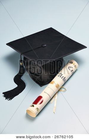 mortar board and the certificate on the plain background