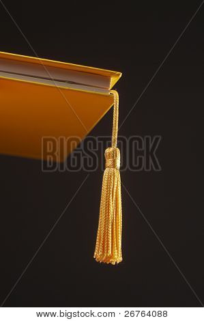 A gold tassel hanging out of a hard cover book on the black background metaphor for Graduation Cap