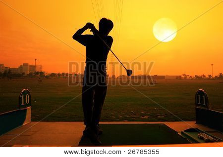 a silhouette of a golfer on a bright sky