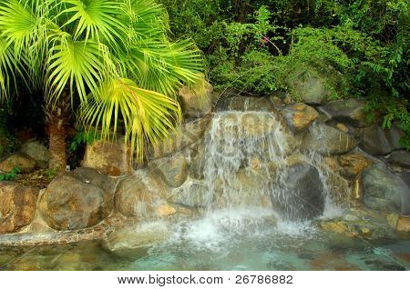 A waterfall in to a pool in a luxury hotspring