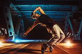 Young cool man break dancer on urban bridge with cool and warm lights background. Tattoo on body. poster