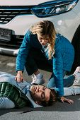 Young Woman Checking Heartbeat Of Victim After Traffic Collision poster
