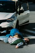High Angle View Of Woman Checking Heartbeat Of Injured Man Lying On Road After Car Accident poster