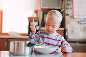 A Handicapped Down Syndrome Child Pouring Soup Into A Plate Indoors. poster