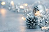 Glowing Christmas Lights Garland And Pine Cone With Jingle Bell On Blurred Silver Background poster