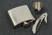 Close Up View Of Set Of Steel Flask, Can Opener And Steel Shot Glass. Beautiful Backgrounds. Steel B poster