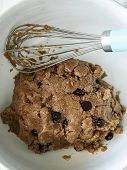 Chocolate chip cookie dough in a bowl with whisk poster
