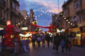 Blurred Background Of Christmas Fair On Old Town Street. Traditional Christmas Market Time Concept W poster