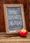 Small Business Saturday sign - white chalk handwriting on a blackboard agains rustic barn wood - hol poster