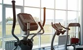 Elliptical Trainer In A Fitness Gym Club With Row Of Trainers For Fitness Cardio Training On The Bac poster