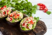 Avocado Appetizers Stuffed With Canned Tuna, Bell Pepper, Herbs On Wooden Cutting Board poster