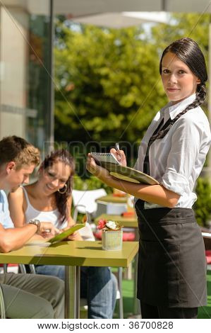 Waitress waiting for clients to decide cafe order restaurant terrace
