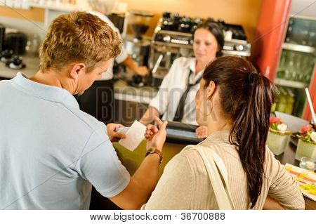 Man checking receipt at cafe restaurant payment waitress couple bar