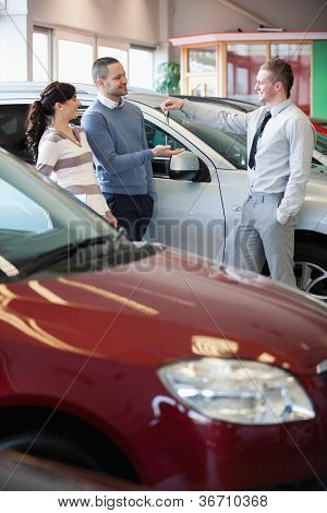 Smiling salesman giving keys to a happy couple in a car shop