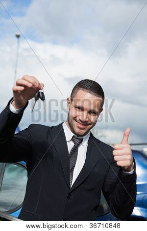 Man holding car keys while raising his thumb outdoors