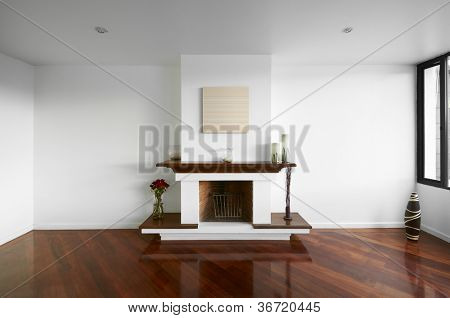 Big empty living room with a chimney, white wall and wooden floor
