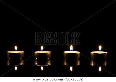 four tea candles on a black mirror
