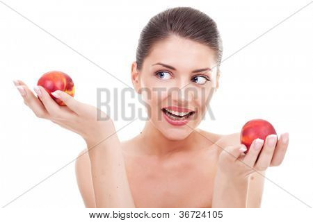 Picture of a gorgeous young woman holding two apples in her hand and watching at one of them. Young woman deciding which apple to choose. Over white background