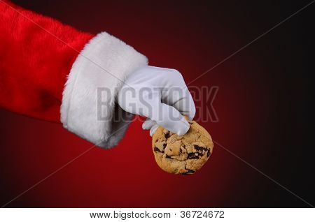 Santa Claus hand holding a chocolate chip cookie over a light to dark red background. Horizontal format showing only hand and arm.