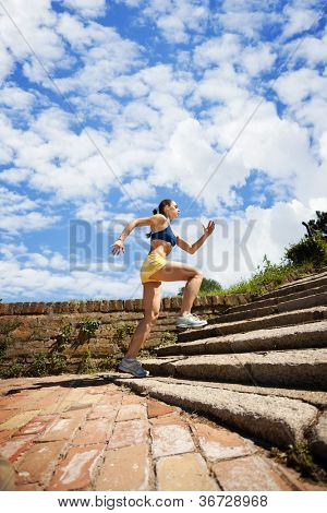 Young woman jogging in nature on steps