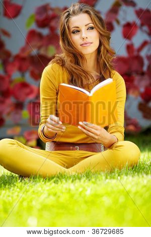 A shot of an european  student studying on campus lawn
